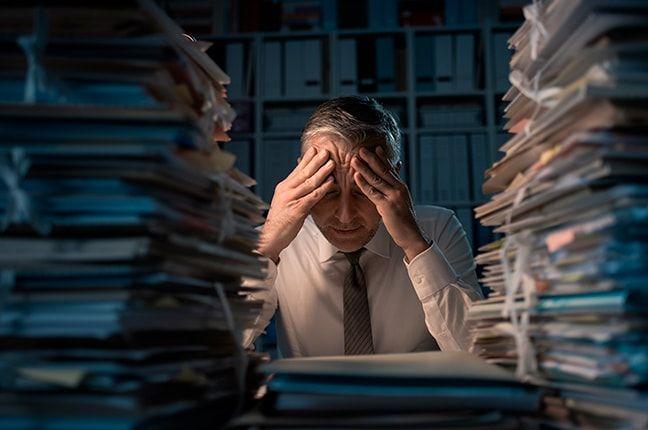 homem em escritório com pilha de arquivos